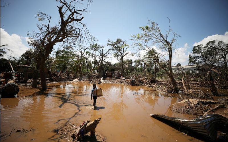 """Uma criança entra na povoação de Buzi, perto da Beira, ao recuarem as águas, após o ciclone """"Idai"""" © Mike Hutchings / REUTERS"""