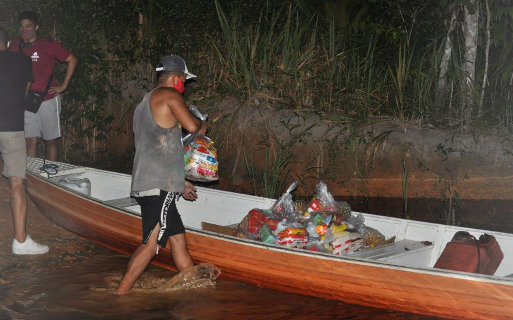 Members of the campaign fill a boat with baskets to offer to the Tururukari Kambeba community. © SOS Amazonia